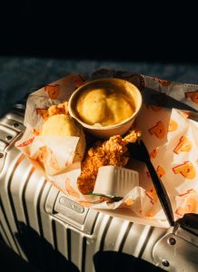 Eating Popeyes Chicken on my Rimowa suitcase while Waiting at the airport for my flight to CDMX - Travelling to Mexico City - Jeff On The Road - Jeff Frenette Photography